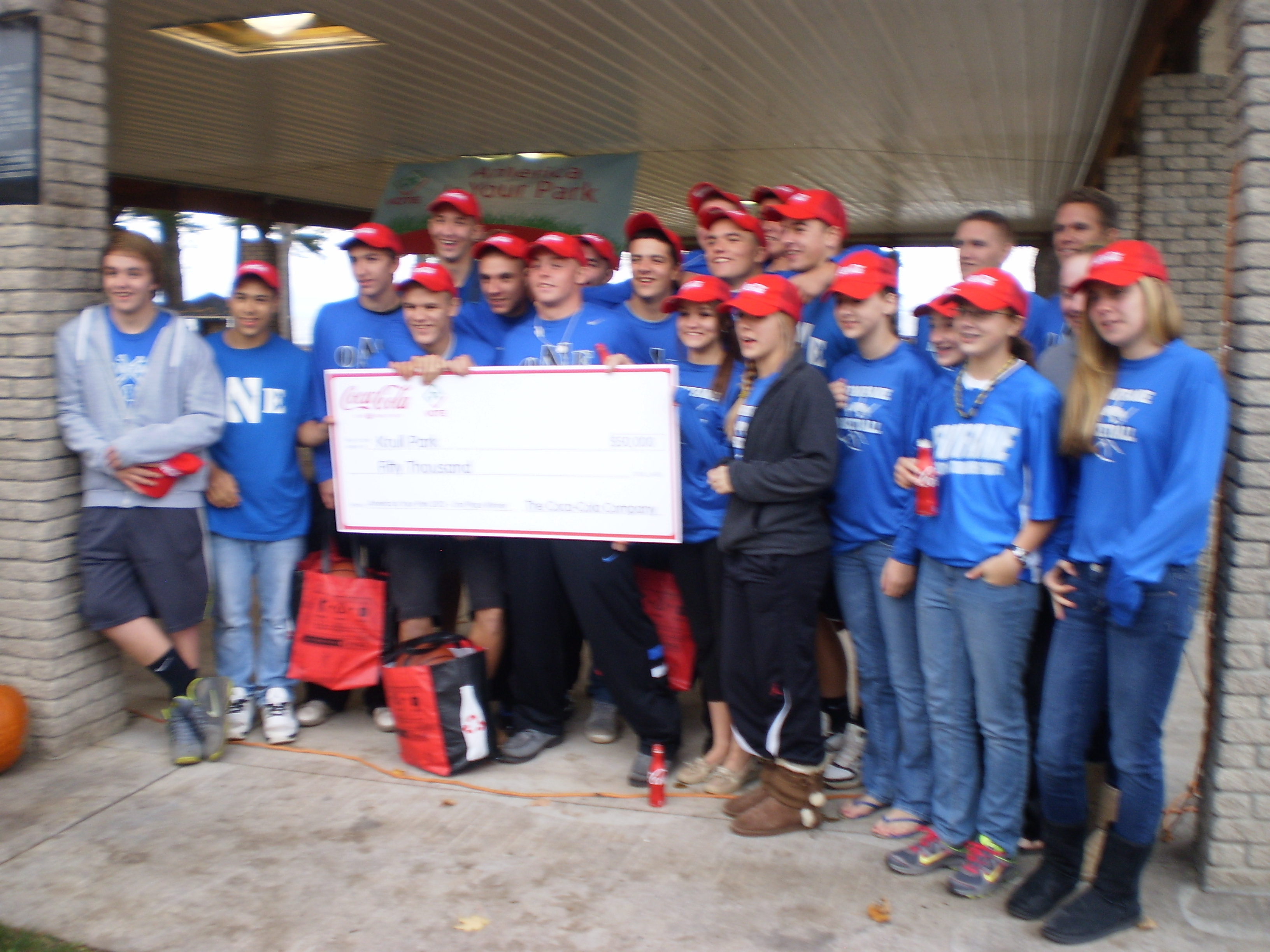 Members of Newfane boys and girls basketball teams holding $50,000 check